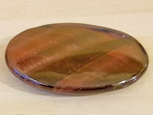 Highly polished Red Tiger Eye palm stone 70 x 40 mm. The palm stones are made from the best grade rough materials to produce a well finished, highly polished product. Used by crystal healers and general therapists for massage and similar treatments. Also perfect for collectors. Being a natural product these stones may have natural blemishes and vary in colour and banding. www.naturalhealingshop.co.uk based in Nuneaton for crystals, spiritual healing, meditation, relaxation, spiritual development,workshops.