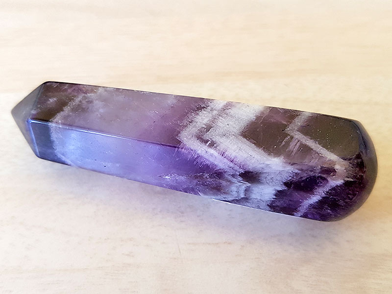 Highly polished Chevron Amethyst wand approximate height 70 mm Used in crystal healing and meditation. Excellent for collectors. Being a natural product this crystal may have natural blemishes and vary in colour. www.naturalhealingshop.co.uk based in Nuneaton for crystals, spiritual healing, meditation, relaxation, spiritual development,workshops.