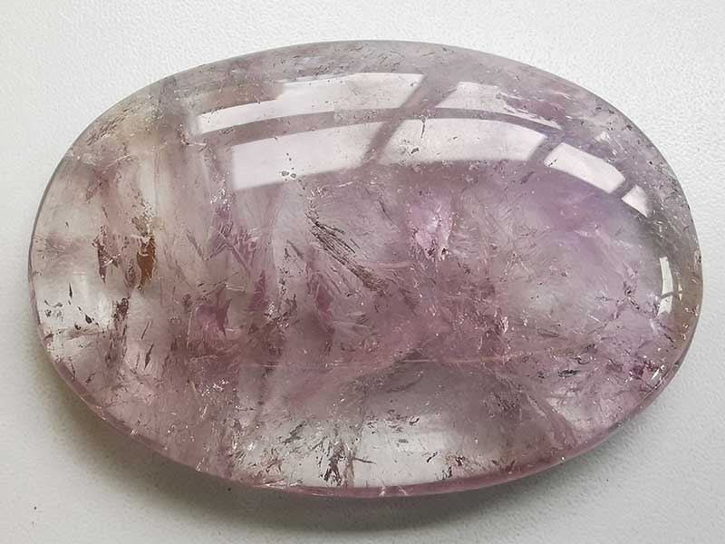 Highly polished Amethyst extra grade palm stone 70 x 50 mm. The palm stones are made from the best grade rough materials to produce a well finished, highly polished product. Used by crystal healers and general therapists for massage and similar treatments. Also perfect for collectors. Being a natural product these stones may have natural blemishes and vary in colour and banding. www.naturalhealingshop.co.uk based in Nuneaton for crystals, spiritual healing, meditation, relaxation, spiritual development,workshops.