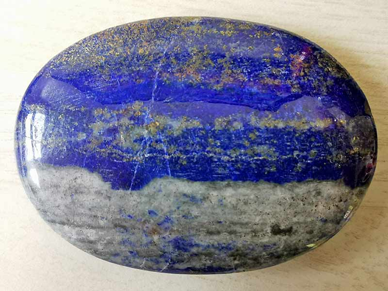 Highly polished Lapis Lazuli comfort stone approx size 60 x 43 mm Being a natural product this crystal may have natural blemishes and vary in colour and banding. www.naturalhealingshop.co.uk based in Nuneaton for crystals, spiritual healing, meditation, relaxation, spiritual development,workshops.